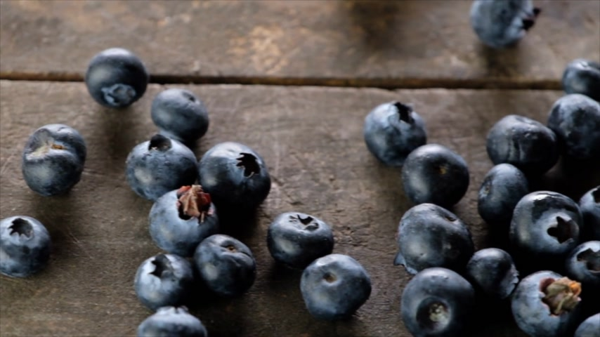 áfonya : Blueberries rolling on a wooden board. Slow motion. Stock mozgókép