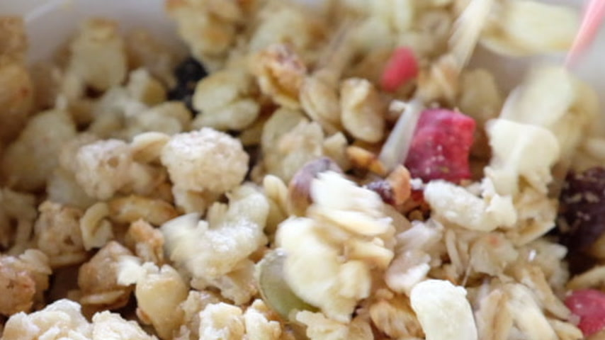 oat flakes : Pouring cereals into a white bowl. Slow motion.