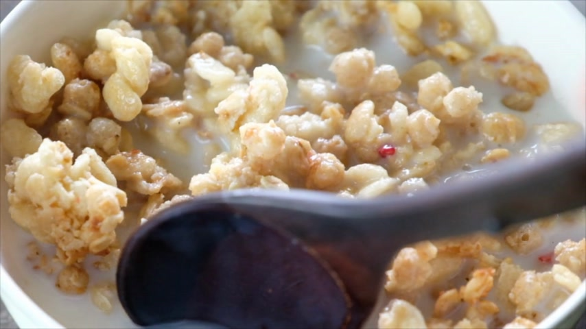 oat flakes : Wooden spoon stirring cereals with blueberry fruits and milk in a bowl. Slow motion.