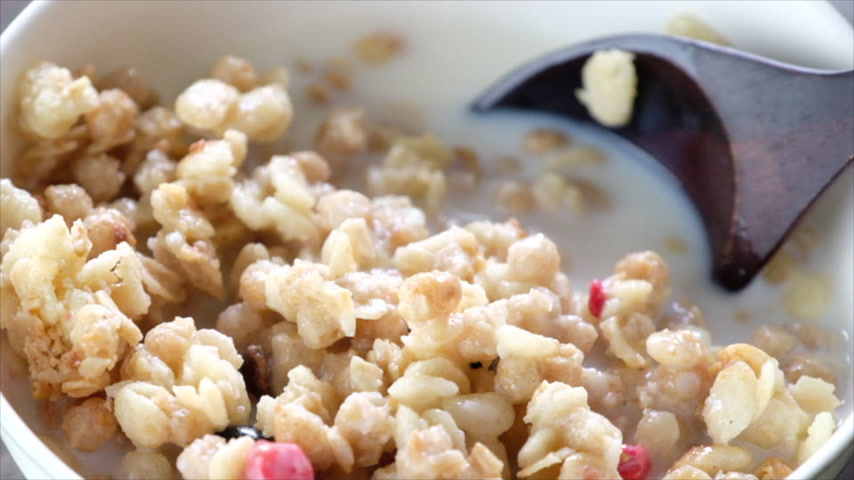 pehely : Wooden spoon stirring cereals with blueberry fruits and milk in a bowl. Slow motion.