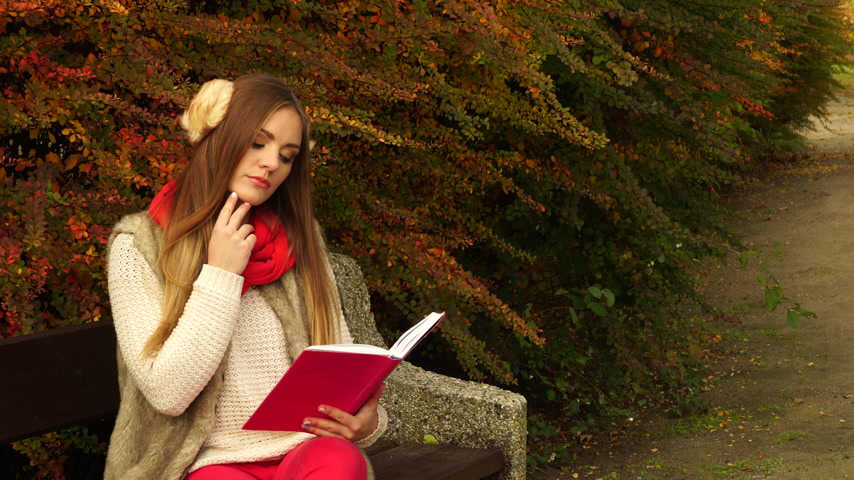 autumnal : Woman fashion girl relaxing in autumnal park reading book sitting on bench. Fall lifestyle concept. 4K ProRes HQ codec Stock Footage