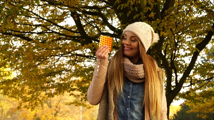 ブリスター : Woman holding pills tablets in autumn fall park forest. Young girl in jacket and scarf giving thumb up gesture. Health care. 4K ProRes HQ codec.