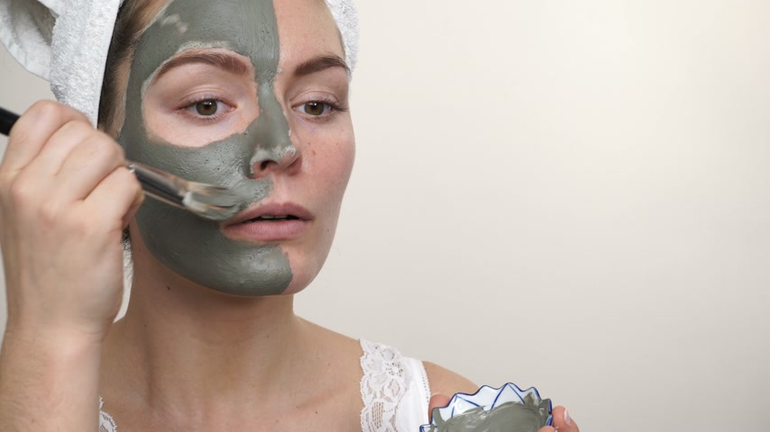 clay mask : Skin care. Woman applying facial brush clay mask to her face studio shot. Girl taking care of oil complexion. Beauty treatment. 4K ProRes HQ codec