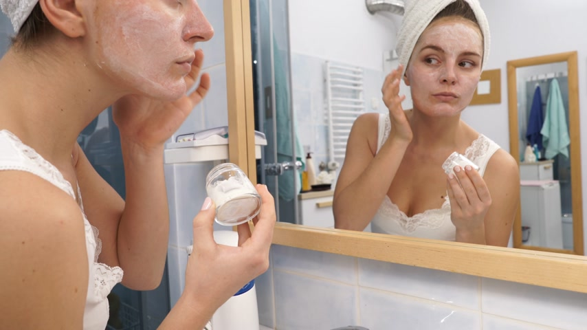 увлажняющий : Woman applying facial moisturizing mask on face looking in mirror. Girl taking care of her complexion layering moisturizer. Skincare spa treatment. 4K ProRes HQ codec