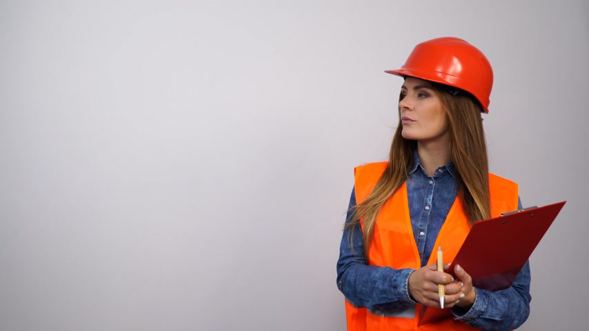 strukturální : Female structural engineer in helmet with notepad and pen thinking. Pretty strong pensive girl working in a man profession. 4K ProRes HQ codec.