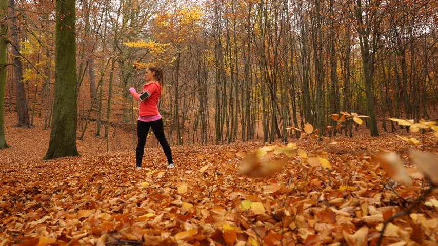 blood sport : Woman warming up in autumn fall park forest. Young girl with smartphone armband activity tracker. Fitness technology. 4K steadicam shot ProRes HQ codec.