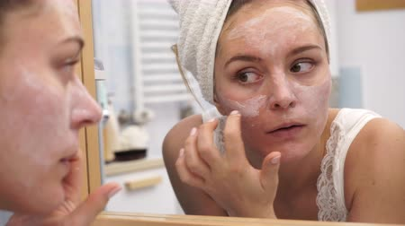 hydratace : Woman applying facial moisturizing mask on face looking in mirror. Girl taking care of her complexion layering moisturizer. Skincare spa treatment. 4K ProRes HQ codec