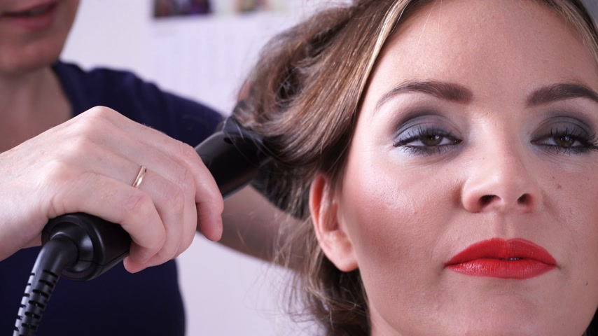 гладильный : Hairdresser curling woman hair with electric iron curler tong. Hairstylist making girl hairstyle. Beauty 4K with motorized slider.