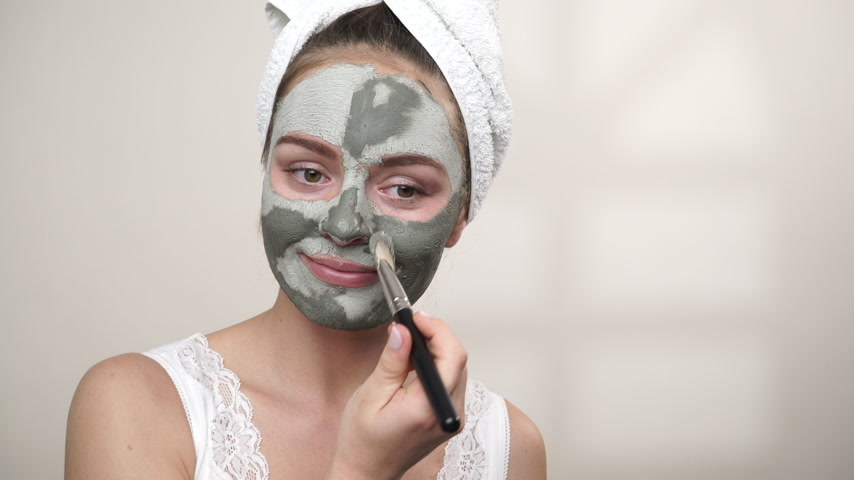 clay mask : Skin care. Woman applying facial brush clay mud mask to her face. Girl taking care of oil complexion. Beauty treatment. 4K ProRes HQ codec Stock Footage