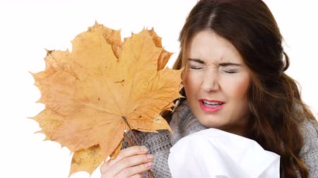 direnç : Sick woman sneezing in tissue holds autumn leaf