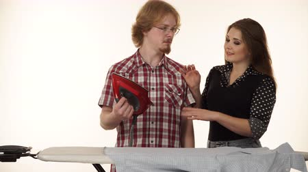 сложены : Funny couple irons clothes on ironing board 4K