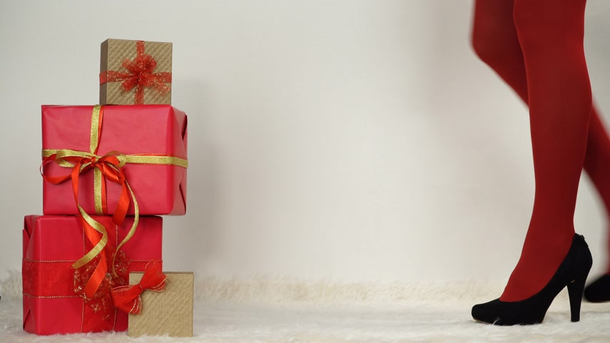 high heel shoe : Woman in high heels and red pantyhose taking present gift. Christmas. 4K ProRes HQ codec.