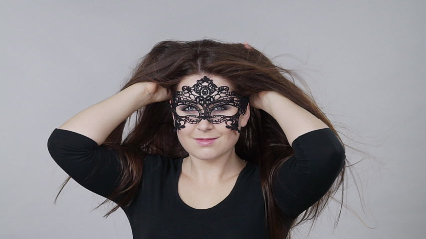 seduce : Woman with carnival mask long hair blowing