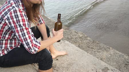 frasco pequeno : Man depressed with wine bottle sitting on beach outdoor. People abuse and alcoholism problems. 4K ProRes HQ codec Vídeos