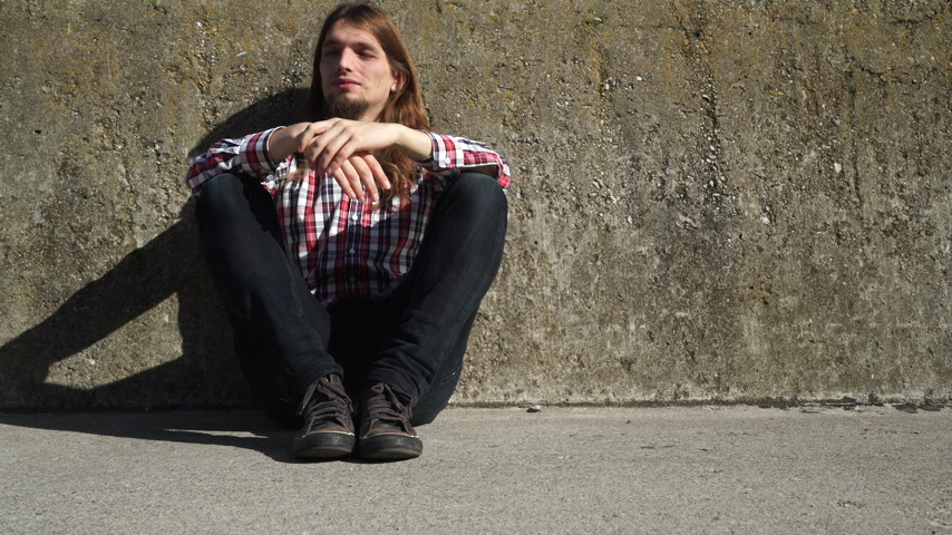 desemprego : Man with long hair sitting by grunge wall outdoor. Unemployment depression or abuse concept. 4K with motorized slider.