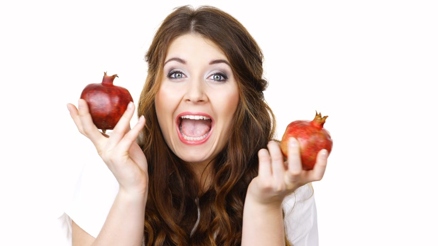 vay : Cheerful woman holds pomegranate fruits, isolated