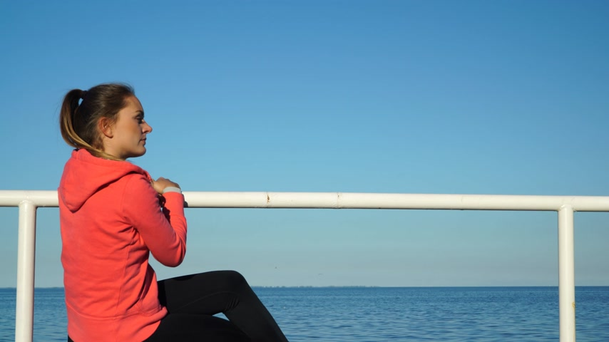 меланхолия : Woman resting after doing sports outdoors. Fitness girl in sportswear sitting on the pier relaxing at the 4K side of the horizon. ProRes HQ codec