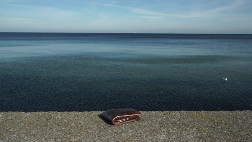 property theft : Man thief finding wallet on the sea shore. Leaving belongings unattended and risk of theft. ProRes HQ codec
