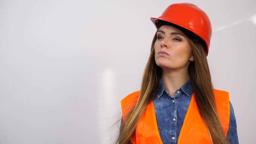 estrutural : Woman structural engineer in helmet thinking. Pretty strong pensive girl working in a man profession. 4K ProRes HQ codec.