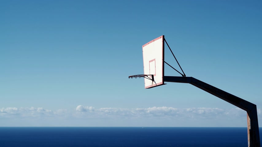 schoolyard : basketball basket on blue sky and sea background Stock Footage