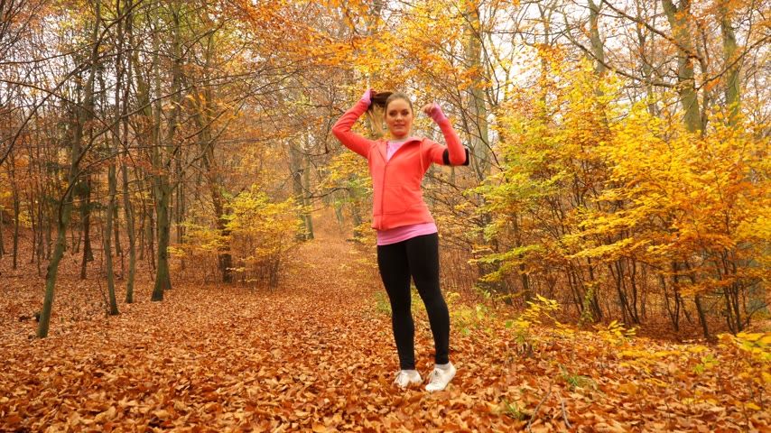 blood sport : Woman warming up in autumn fall park forest. Young girl with smartphone armband activity tracker. Fitness technology. 4K ProRes HQ codec.