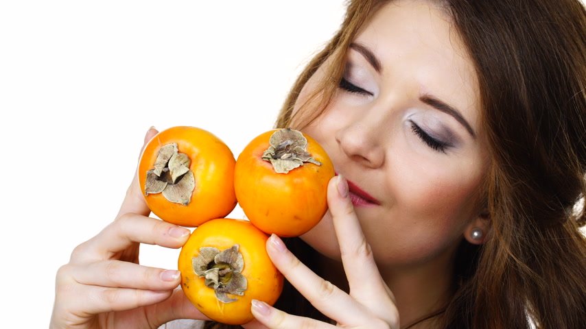 vitamin c : Woman holds persimmon kaki fruits, isolated