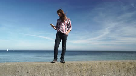 goes : Man long haired casual style walking cell phone, guy using smartphone blue sky background 4K ProRes HQ codec