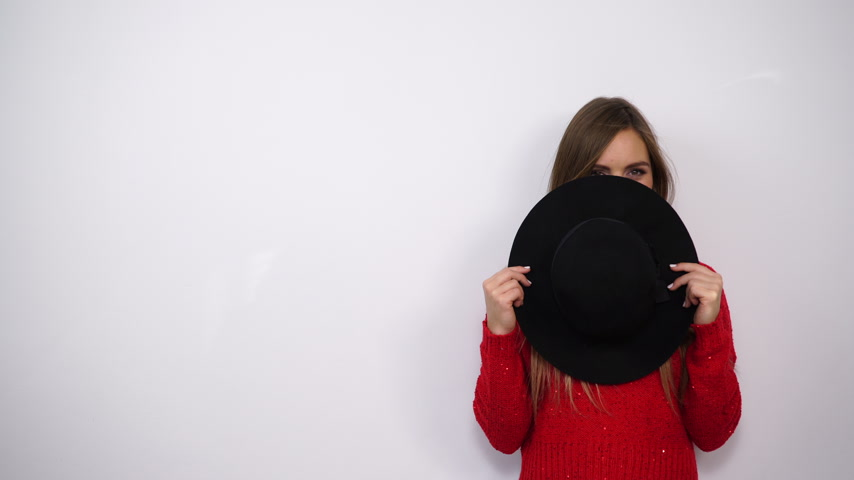 hiding : Woman in red sweater covering face with black hat. Playful fashion young girl having fun. 4K ProRes HQ codec.