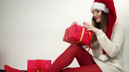 колготки : Woman packing wrapping present gift tying ribbon bow. Happy girl in red santa helper hat. 4K ProRes HQ codec. Стоковые видеозаписи