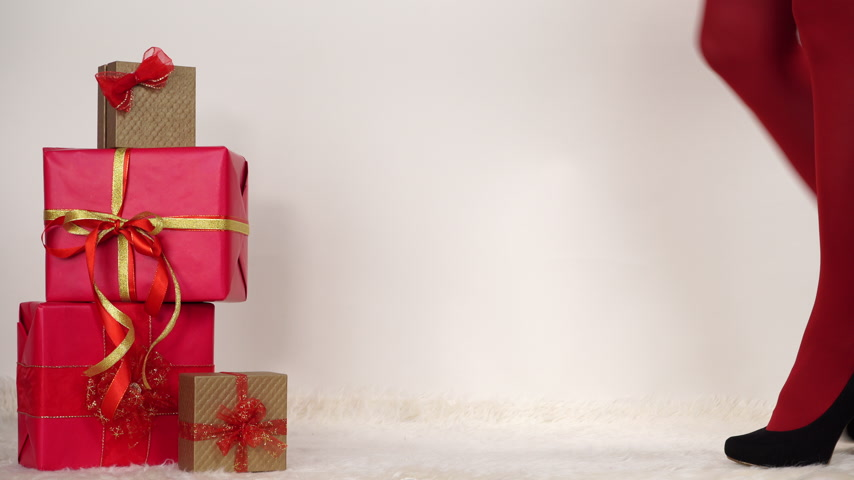 highheels : Woman in high heels shoes and red pantyhose opening gift present box. Christmas season. 4K ProRes HQ codec.