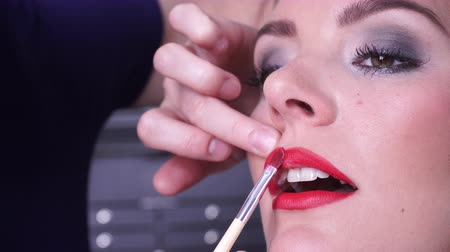 átalakítása : Cosmetic beauty procedures. Closeup woman face red lips. Makeup artist applying lipstick is a model lip with brush accessories tools 4K
