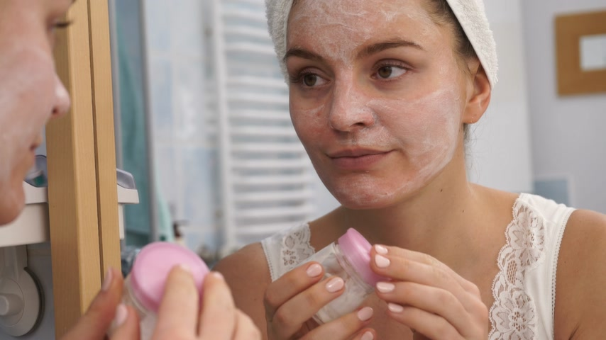 melisa : Woman applying facial moisturizing mask on face looking in mirror. Girl taking care of her complexion layering moisturizer. Skincare spa treatment. 4K ProRes HQ codec