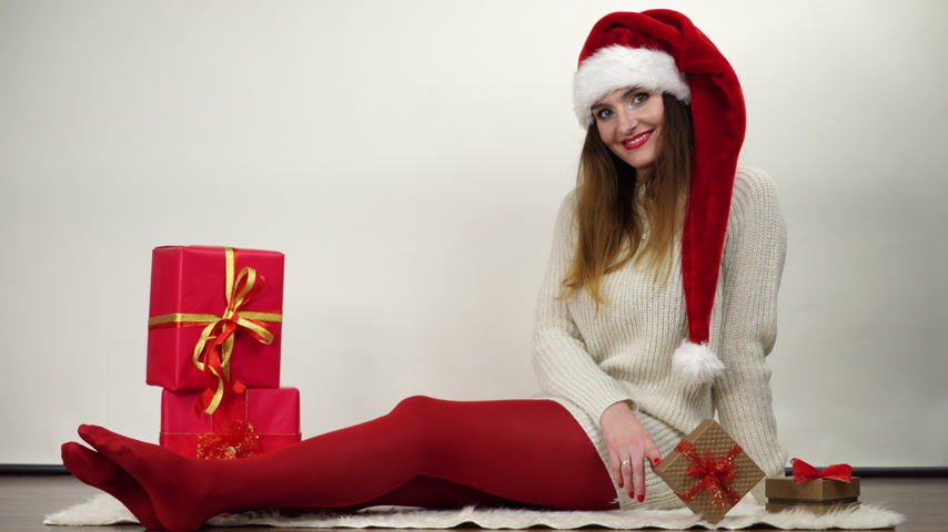 punčocháče : Woman in red pantyhose and santa claus helper hat with christmas gifts presents. Happy attractive girl wearing tights. 4K ProRes HQ codec.