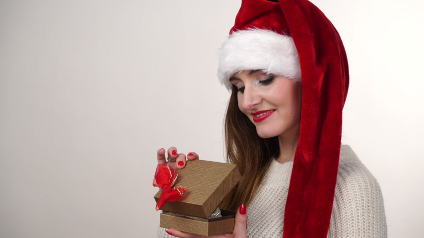 presentes : Woman in santa claus helper hat opening gift present box. Christmas season. 4K ProRes HQ codec.