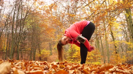 согревание : Woman warming up in autumn fall park forest. Young girl with smartphone armband activity tracker. Fitness technology. 4K ProRes HQ codec.