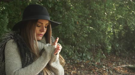 замораживать : Woman outdoor. Fashionable autumn girl with long hair in black hat walking on nature. Beauty female model in the park warming her hands 4K Prores HQ codec Стоковые видеозаписи