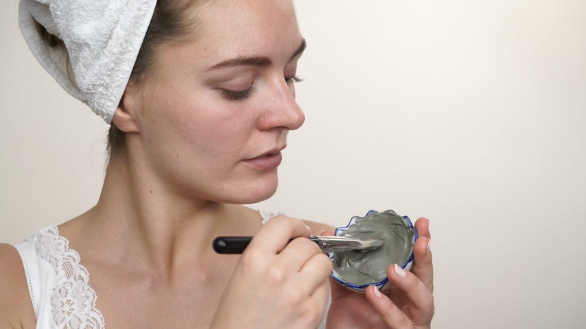 soyulması : Skin care. Woman applying facial brush clay mask to her face studio shot. Girl taking care of oil complexion. Beauty treatment. 4K ProRes HQ codec