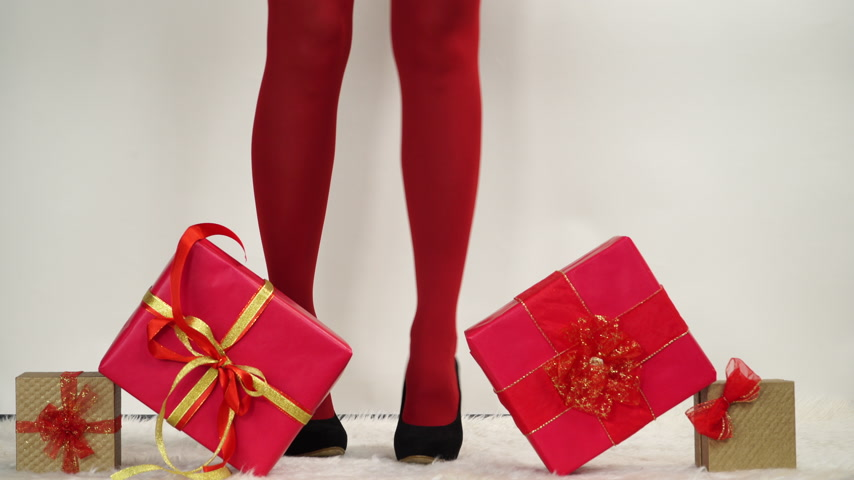 stockings : Woman in high heels shoes and red pantyhose taking presents gifts. Christmas. 4K ProRes HQ codec.