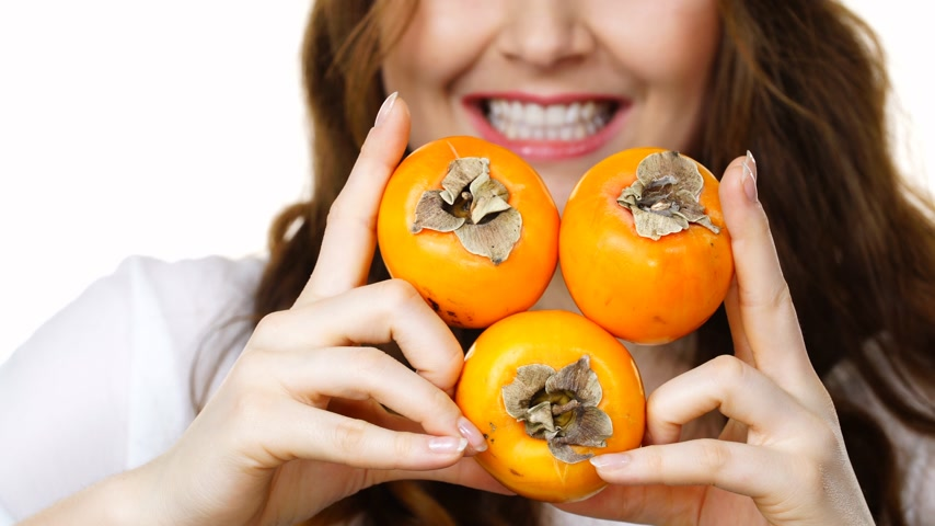 kaki : Cheerful woman holds persimmon kaki fruits, isolated