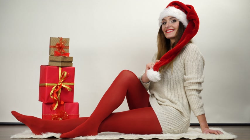 колготки : Woman in red pantyhose and santa claus helper hat with christmas gifts presents. Happy attractive girl wearing tights. 4K ProRes HQ codec.