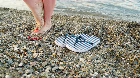 görög : Woman feet with flip flops on beach shore