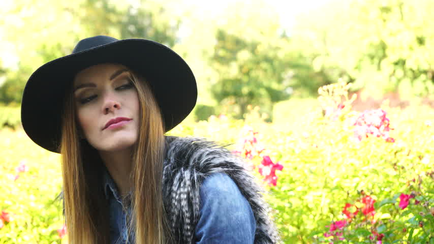 devanear : Woman sad outdoor. Thoughtful girl wearing stylish black hat in park 4K Prores HQ codec Stock Footage
