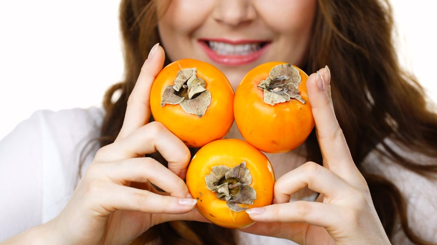 apetite : Cheerful woman holds persimmon kaki fruits, isolated