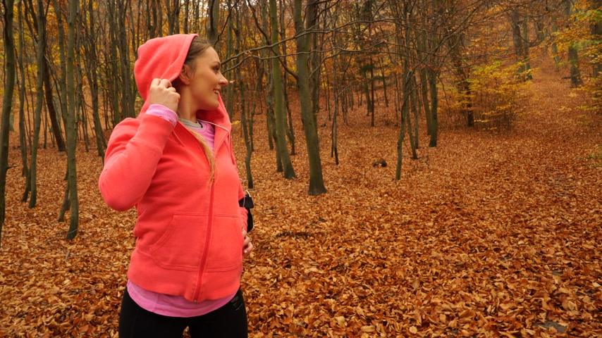 blood sport : Woman runner jogger in autumn park fall forest with smartphone app. Young girl with activity tracker armband. Fitness technology. 4K steadicam shot ProRes HQ codec.