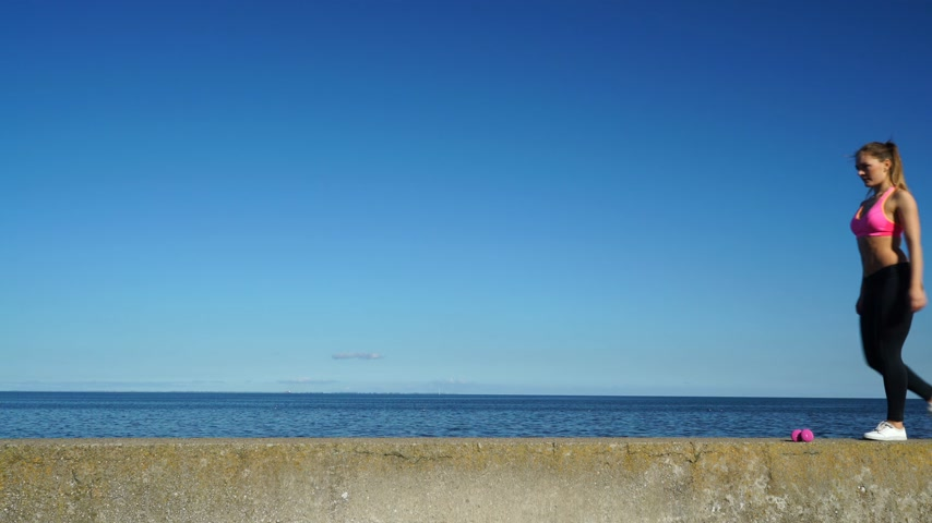 intenzivní : Woman doing sports outdoors. Fitness girl in sportswear on the seaside. 4K. ProRes HQ codec