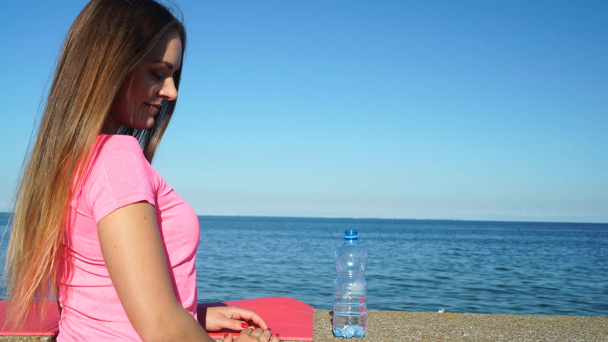 cansado : Woman drinking water from plastic bottle. Fitness girl in sportswear on the seaside. 4K. ProRes HQ codec Stock Footage
