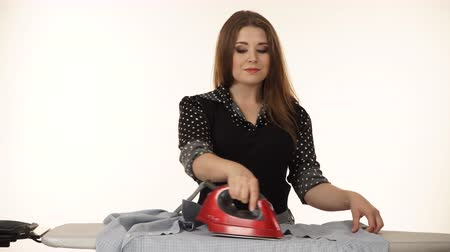 lavanderia : Happy woman using iron on ironing board 4K Stock Footage