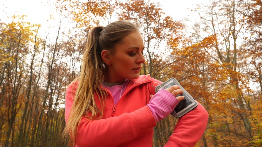 blood sport : Woman running jogging in autumn park fall forest setting smartphone app. Young girl with activity tracker armband. Fitness technology. 4K steadicam shot ProRes HQ codec. Stock Footage