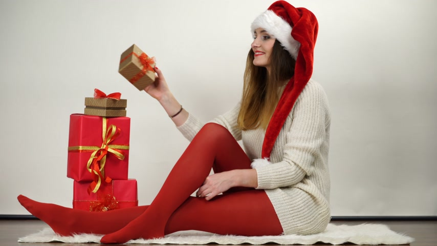 колготки : Woman in red pantyhose and santa claus helper hat unpacking christmas present. Happy attractive girl wearing tights. 4K ProRes HQ codec.