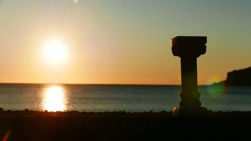 peloponnese : Greek column on the shore and sunset over the sea surface
